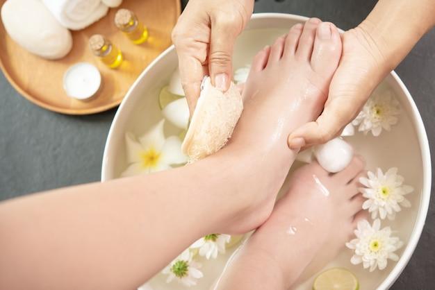 Lavaggio dei piedi nella spa prima del trattamento. trattamento termale e prodotto per piedi femminili e spa per le mani. Foto Gratuite