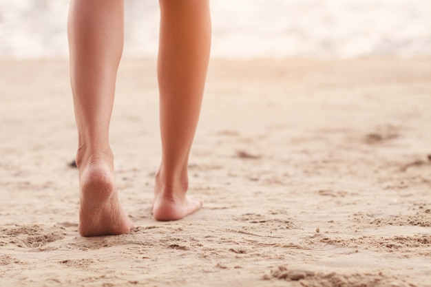 Foot of woman walking on the beach. Premium Photo