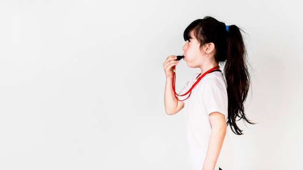 Football concept with girl using whistle and copyspace Free Photo