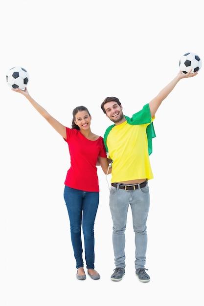 Football fan couple cheering and smiling at camera Premium Photo
