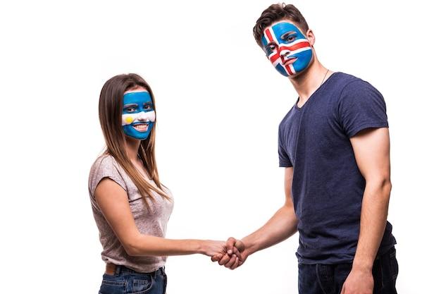 塗られた顔を持つアルゼンチンとアイスランドの代表チームのサッカーファンは、白い背景の上で握手します 無料写真