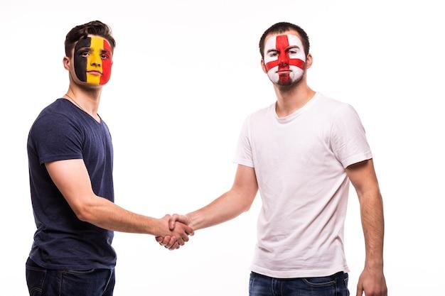 塗装された顔を持つベルギーとイギリスの代表チームのサッカーファンは、白い背景の上で握手します 無料写真