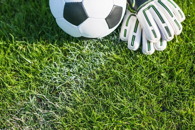 Football in grass with gloves Free Photo