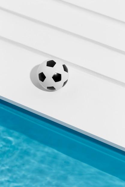 スイミングプールの横にあるサッカー 無料写真