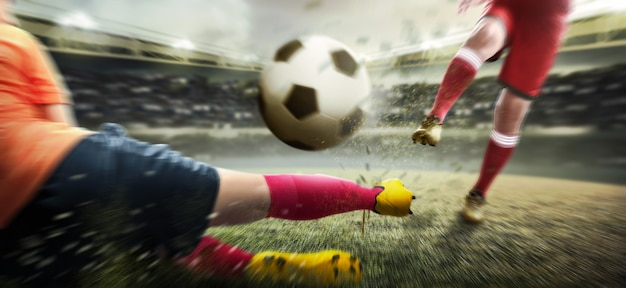 Football player man kicking the ball when his opponent trying to tackle the ball Premium Photo
