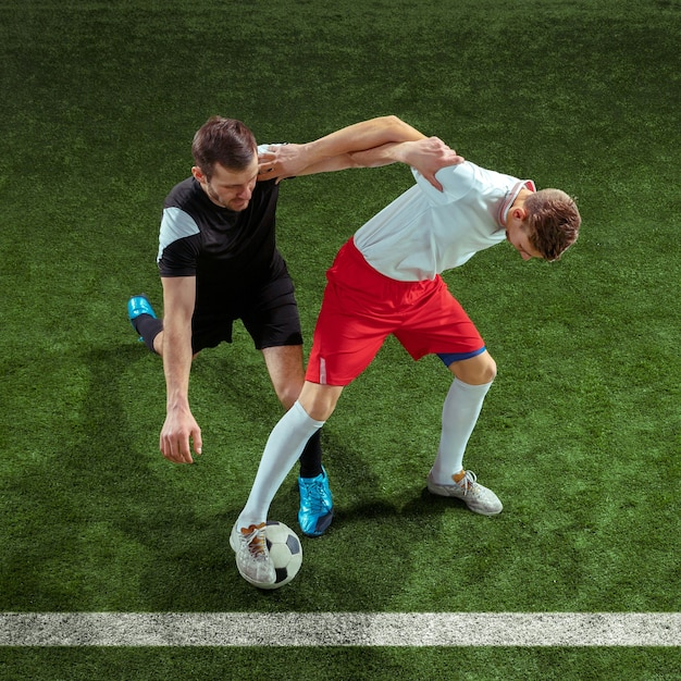 Football player tackling for ball over green grass wall. professional male soccer players in motion at stadium. fit jumping men in action, jump, movement at game. Free Photo