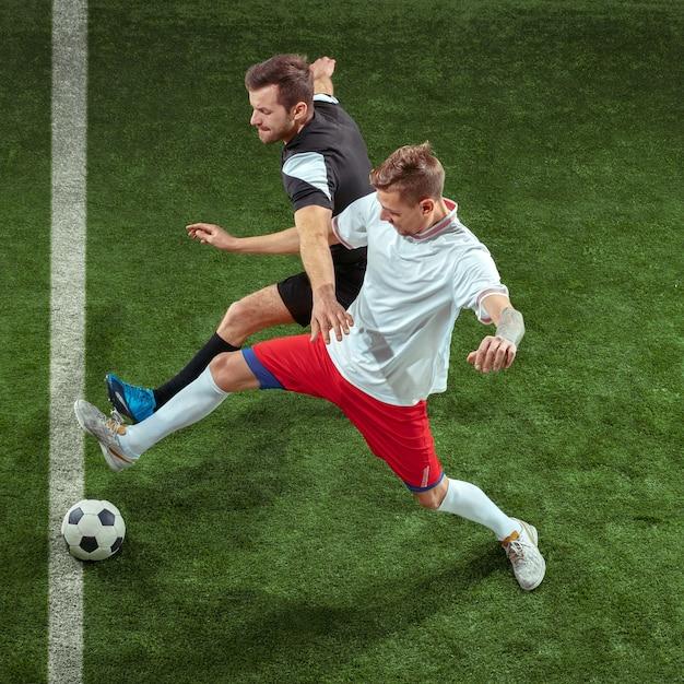 緑の芝生の壁を越えてボールに取り組むフットボール選手。スタジアムで動いているプロの男子サッカー選手。ジャンプする男性をアクション、ジャンプ、ゲームでの動きに合わせます。 無料写真