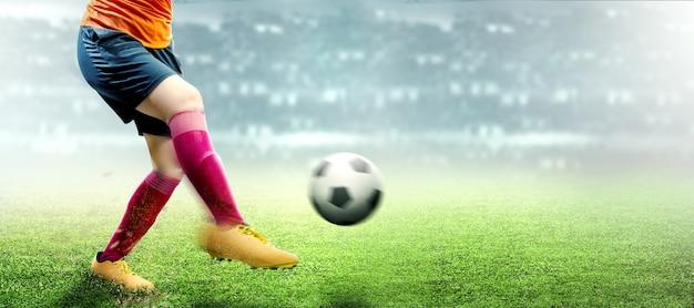 Football player woman in orange jersey kicking the ball Premium Photo
