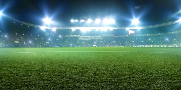 Футбольный стадион, блестящие огни, вид из полевой травы. газон, никого на детской площадке, трибуны с любителями игр в космосе Premium Фотографии