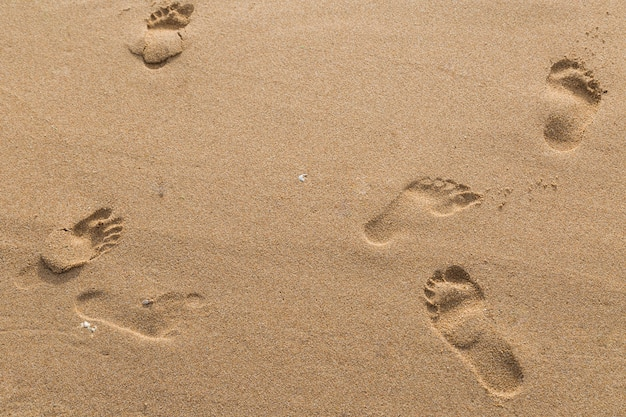 Footprints of lovers in the sand on the beach  background Premium Photo