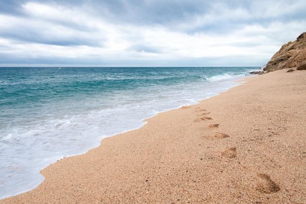 空のビーチで砂の上の足跡。海の波は砂の足跡を洗います Premium写真
