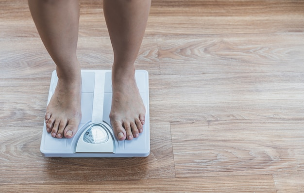 Foots of asian woman on weight scale,lose weight concept Premium Photo
