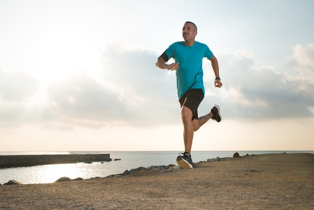 Forceful young man enjoying running outdoors Free Photo