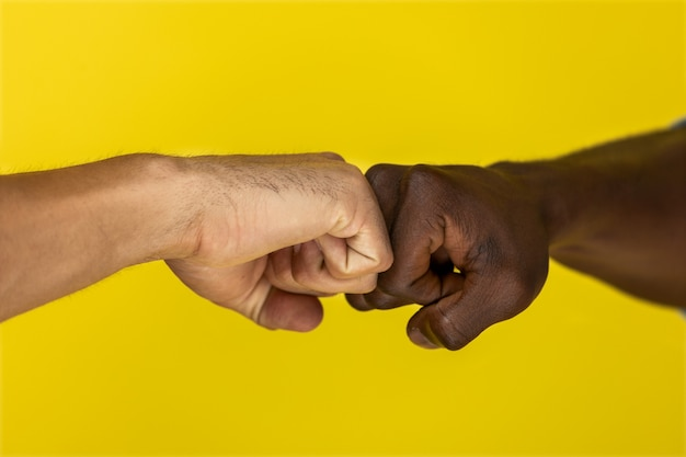 Foreground european and afroamerican hand to hand clenched into fists Free Photo