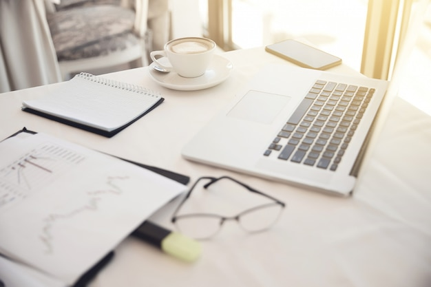 Foreground of objects on the working place: eyeglasses, diagrammes, laptop, notebook Free Photo