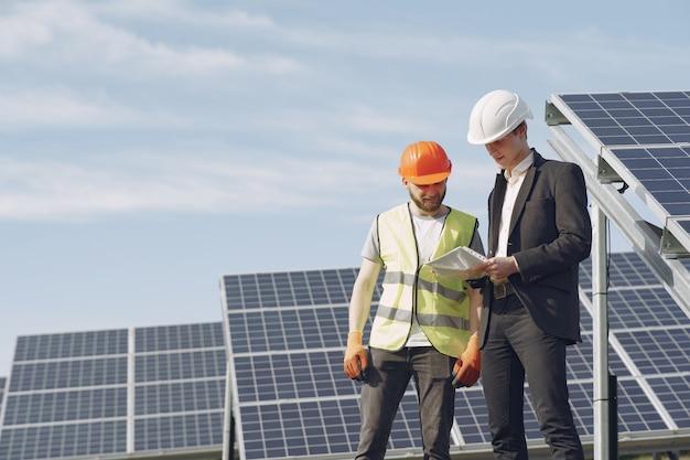Форман и бизнесмен на станции солнечной энергии. Бесплатные Фотографии