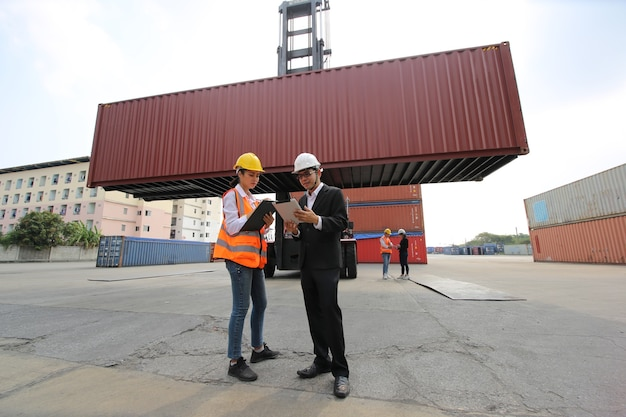 Foreman control loading containers box from cargo freight ship for import export. container warehouse worker. Premium Photo