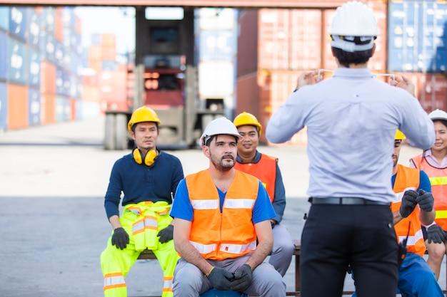 フォアマンは、コロナウイルスが蔓延している間、フェイスマスクを着用し、自分の世話をする方法を労働者に教え、訓練しています。 Premium写真