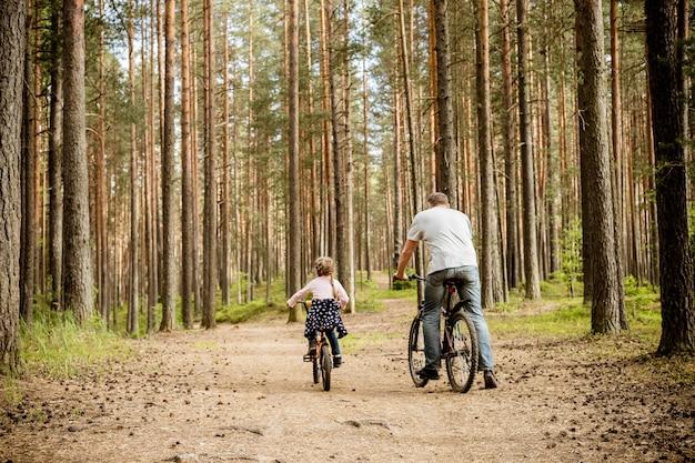 Задний взгляд катания отца и дочери велосипеды вокруг forest.young семья в лете задействуя в парке. семья темы резвится напольное воссоздание. концепция отдыха приключения. Premium Фотографии