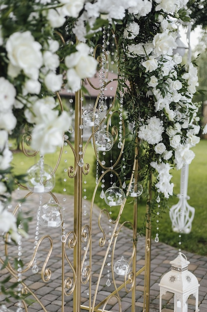 Forged gates are decorated with fresh white flowers and greenery Free Photo