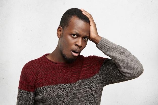 忘れっぽくて無知な若いアフリカ系アメリカ人男性は、ショックと欲求不満で口を開けているカジュアルなセーターに身を包み、額に平手打ちをし、結婚記念日を忘れた 無料写真