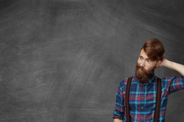 Studente barbuto smemorato che indossa una camicia a scacchi elegante che sembra confuso e perplesso durante la lezione, grattandosi la testa, cercando di ricordare la risposta giusta, in piedi in classe alla lavagna Foto Gratuite