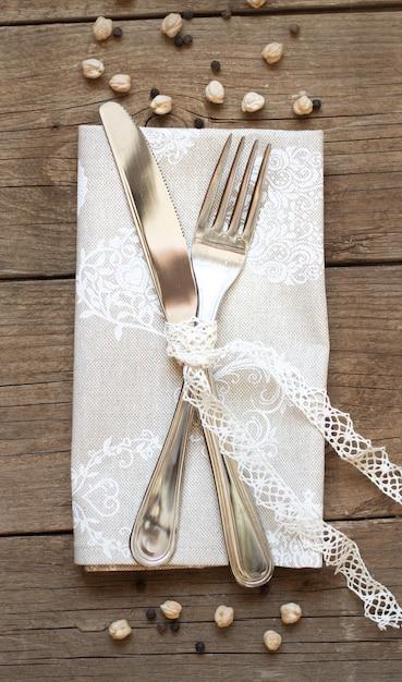 Вилка и нож на салфетке на старый деревянный стол сверху Premium Фотографии