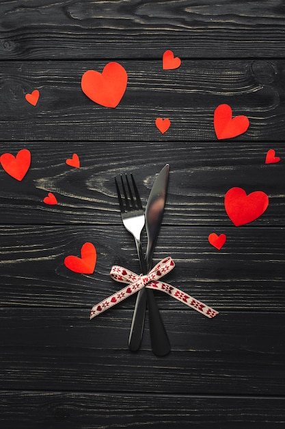 Fork and knife on table with hearts Free Photo