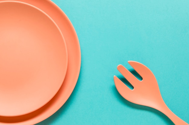 Fork and plates on blue background Free Photo