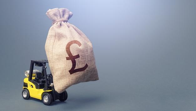 Вилочный погрузчик с мешком денег в британских фунтах стерлингов. сильная финансовая помощь Premium Фотографии