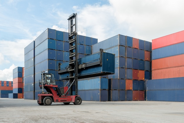 Forklift lifting container box loading to container depot use for cargo import, export, logistics Premium Photo