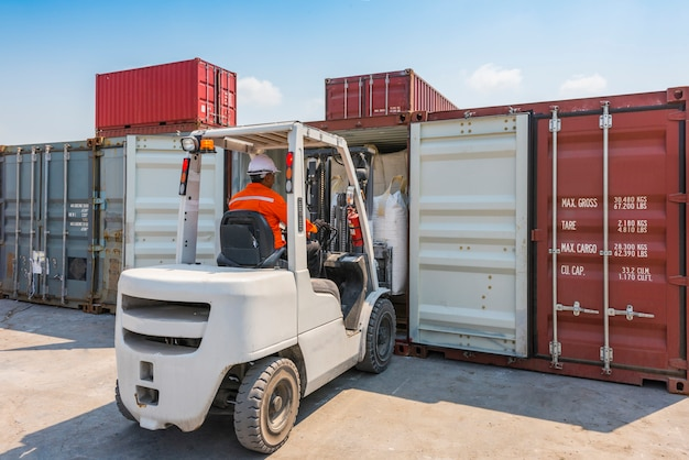 Forklift loading goods to container box in warehouse area Premium Photo