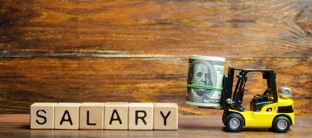 Forklift truck carries a bundle of dollars to the inscription salary Premium Photo