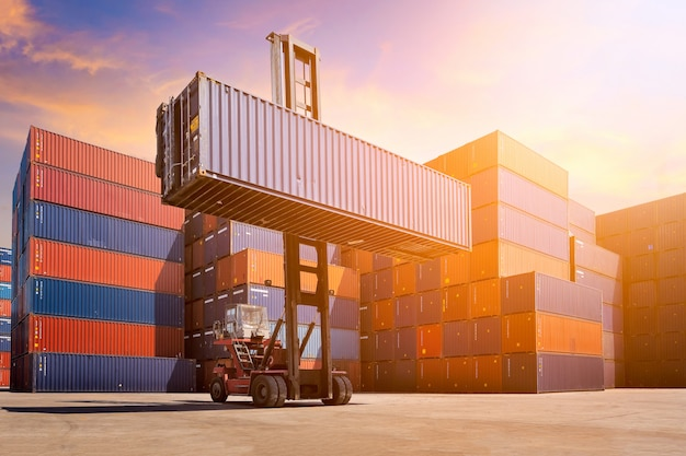 Forklift truck lifting cargo container in shipping yard Premium Photo