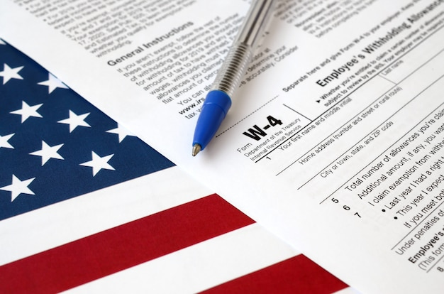 Form w-4 employee's withholding allowance certificate and blue pen on united states flag. internal revenue service tax form Premium Photo