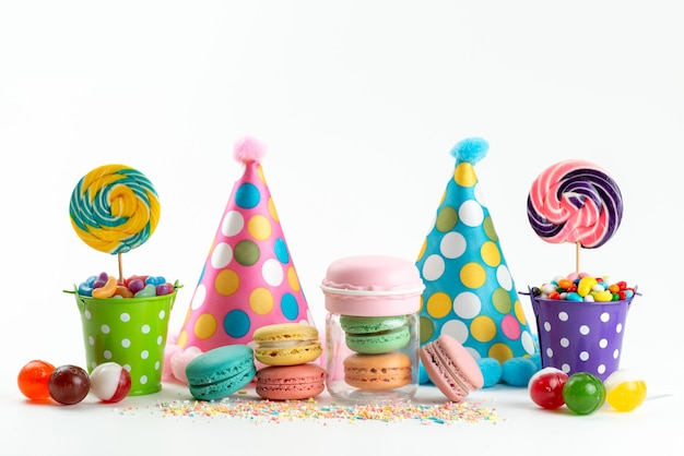 A fornt view delicious french macarons along with birthday caps candies and lollipops on white, celebration birthday biscuit Free Photo