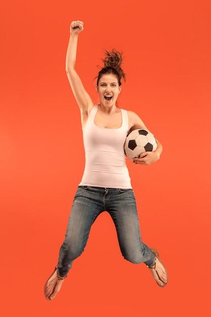 勝利に向けて。赤い背景のスタジオでジャンプしてボールを蹴るサッカーサッカー選手としての若い女性。サッカーファンと世界選手権のコンセプト。人間の感情の概念 無料写真
