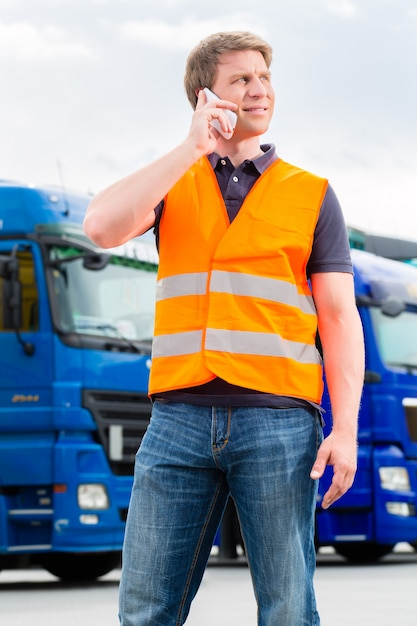 Forwarder in front of trucks on a depot Premium Photo