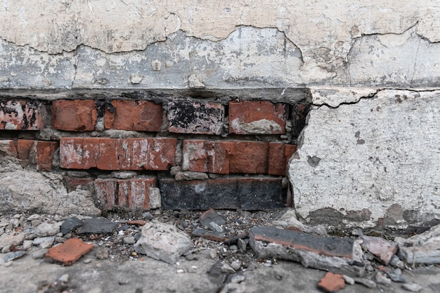 The foundation of a residential building is gradually collapsing. cracks in the foundation. plaster falling off of a brick wall due to the impact of weather factors. Premium Photo
