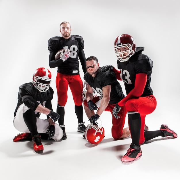 I quattro giocatori di football americano che posano con la palla su spazio bianco Foto Gratuite