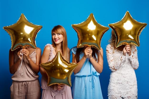 Четыре красивые девушки отдыхают на вечеринке над синей стеной Бесплатные Фотографии