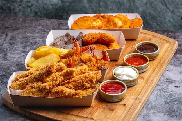 Четыре коробки самородков с сыром из куриных креветок и рыбы с четырьмя соусами Бесплатные Фотографии