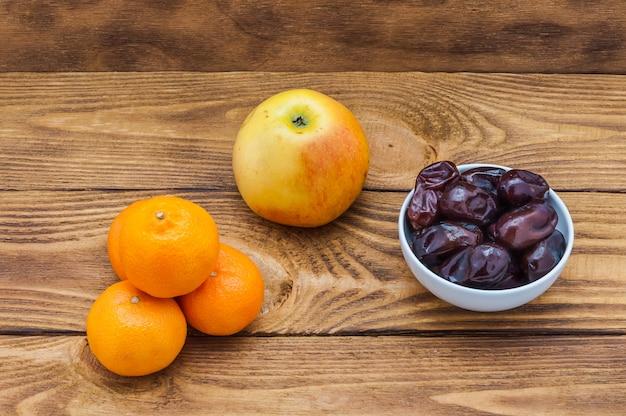 4つの明るいオレンジ色の熟したみかん、リンゴと木のテーブルの上の日付を持つカップ。 Premium写真
