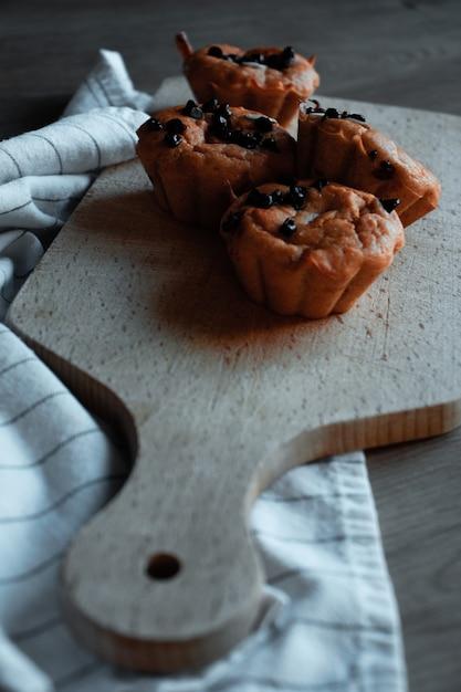 Четыре коричневых кекса на коричневой деревянной разделочной доске Бесплатные Фотографии