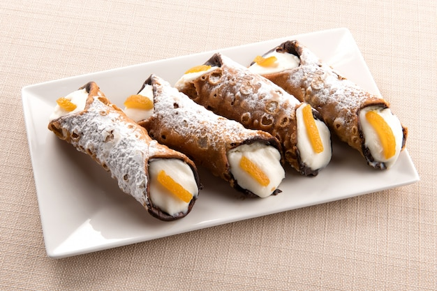 Four cannoli sicilia with creamy ricotta filling Premium Photo