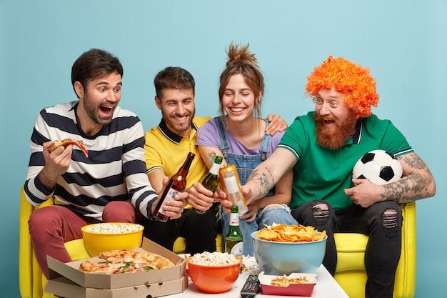 Quattro allegri amici tintinnano bottiglie di birra, hanno tempo libero insieme, guardano la partita di calcio o trasmettono eventi sportivi in tv a casa, mangiano popcorn, pizza e patatine sul tavolo, tifano per la squadra preferita Foto Gratuite
