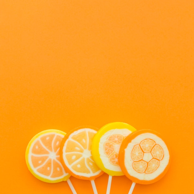 Four citrus fruit lollipops at the bottom of orange backdrop Free Photo