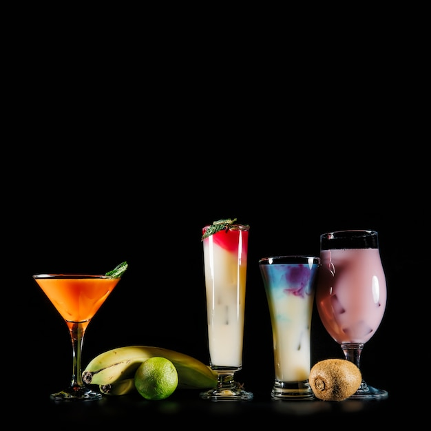 Four Cocktails And Exotic Fruits On Black Background Photo