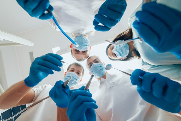 Four dentist in uniform perform dental implantation operation on a patient at dentistry office Premium Photo