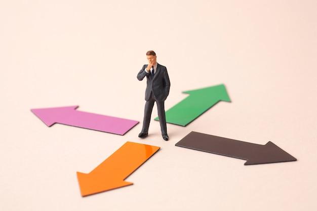 ミニチュアビジネス人と4つの方向矢印 Premium写真